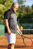 Un uomo calvo di mezza età gioca a tennis sulla corte all'aperto Giorno pieno di sole verticale fotografie stock libere da diritti