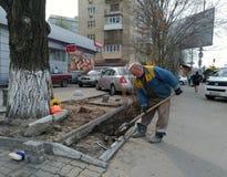 Un uomo in camici che scava un città-letto con una pala fotografia stock