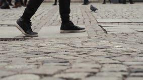 Un uomo cammina con i piedi con i piedi vicini su un viaggiatore su una strada del blocco archivi video
