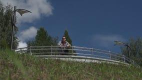 Un uomo cammina lungo l'argine dello stagno della città stock footage
