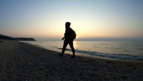 Un uomo cammina lungo la costa al tramonto video d archivio