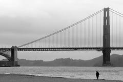 Un uomo cammina sulla spiaggia sotto golden gate bridge in San F Fotografia Stock