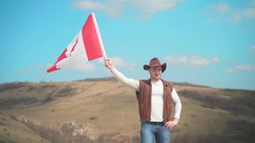 Un uomo in un cappello, una maglia e un bomber ed i jeans sta tenendo una bandiera canadese La bandiera del Canada si sviluppa ne archivi video