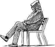 Un uomo in un cappuccio si siede su un banco di parco Immagine Stock Libera da Diritti