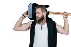Un uomo carismatico con una barba sta tenendo una chitarra elettrica, su un fondo isolato bianco Struttura orizzontale fotografia stock