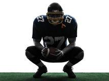 Siluetta accovacciantesi dell'uomo del giocatore di football americano immagine stock