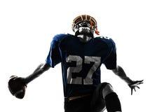 Siluetta trionfante dell'uomo del giocatore di football americano fotografia stock libera da diritti