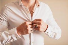 Un uomo che abbottona la sua camicia Fotografia Stock