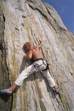 Un uomo che arrampica un fronte della roccia Immagini Stock Libere da Diritti
