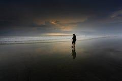 Un uomo che cammina ad una spiaggia Fotografie Stock Libere da Diritti