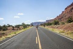 Un uomo che cammina in mezzo alla strada in regione selvaggia dell'Utah immagine stock libera da diritti
