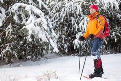 Un uomo che cammina nella neve con uno zaino Fotografia Stock Libera da Diritti