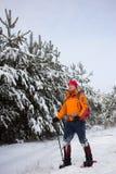 Un uomo che cammina nella neve con uno zaino Fotografia Stock