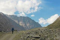 Un uomo che cammina nelle montagne da solo fotografia stock