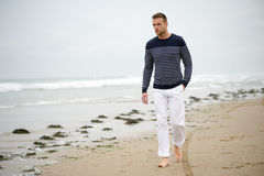Un uomo che cammina sulla spiaggia Immagine Stock Libera da Diritti