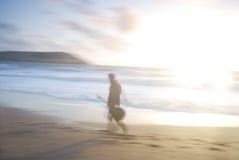Un uomo che cammina sulla spiaggia con la chitarra. Fotografia Stock