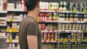 Un uomo che cammina in un supermercato stock footage