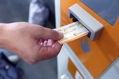 Un uomo che convalida biglietto in una punzonatrice per il treno Barcellona, Spagna fotografie stock