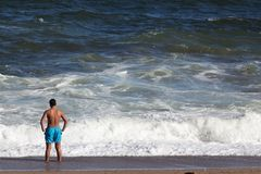 Un uomo che esamina il mare nella spiaggia, retrovisione fotografie stock