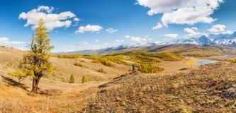 Un uomo che esamina le montagne e un lago qui sotto dal punto di vista Immagini Stock