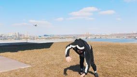 Un uomo che esegue i trucchi acrobatici sull'erba stock footage