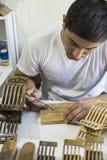 Un uomo che fa un supporto di libro di legno dal legno rihals Fotografie Stock Libere da Diritti