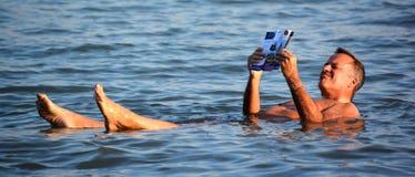 Un uomo che galleggia nell'acqua salata del mar Morto Fotografie Stock Libere da Diritti