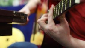 Un uomo che gioca chitarra acustica con un plettro video d archivio