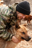 Un uomo che gioca con un cane immagini stock