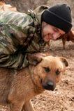 Un uomo che gioca con un cane Fotografia Stock