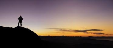 Un uomo che gioca gli sport nelle montagne al tramonto Fotografie Stock