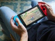 Un uomo che gioca Mario Kart 8 di lusso sul commutatore di Nintendo immagini stock libere da diritti