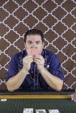 Un uomo che gioca poker che si siede ad una tavola Fotografie Stock Libere da Diritti