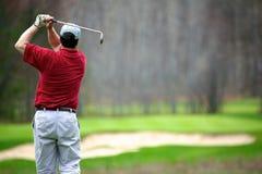 Un uomo che gode di un gioco di golf fotografia stock