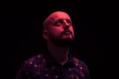 Un uomo che guarda sopra su, luce di colore rosso Fotografia Stock