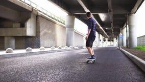 Un uomo che guida un pattino sull'asfalto sui precedenti del passaggio stock footage