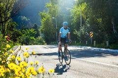 Un uomo che guida una bicicletta su una strada della montagna fotografia stock libera da diritti