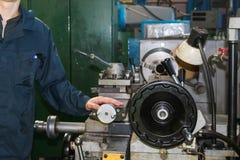 Un uomo che lavora in un abito, camici sta accanto ad un tornio industriale per il taglio, girante i coltelli dai metalli, legno  immagine stock libera da diritti