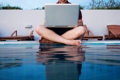 Un uomo che lavora al computer portatile, sedentesi al poolside, fuoco selettivo Immagine Stock