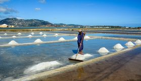 Un uomo che lavora al giacimento del sale nel Vietnam fotografia stock