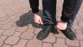 Un uomo che lega i laccetti sulle scarpe che camminano nel parco di estate stock footage