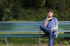 Un uomo che legge un e-lettore su un banco Immagini Stock