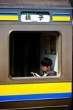 Un uomo che legge un libro sul treno fotografia stock