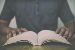Un uomo che legge un libro sulla tavola di legno con il filtro d'annata ha offuscato il fondo Fotografie Stock