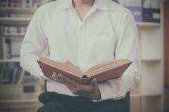 Un uomo che legge un libro sulla tavola di legno con il filtro d'annata ha offuscato il fondo Immagini Stock Libere da Diritti