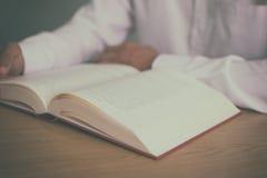 Un uomo che legge un libro sulla tavola di legno con il filtro d'annata ha offuscato il fondo Immagine Stock Libera da Diritti