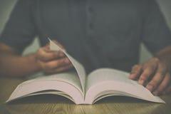 Un uomo che legge un libro sulla tavola di legno mentre lanciare le pagine con il filtro d'annata ha offuscato il fondo Immagine Stock