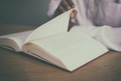 Un uomo che legge un libro sulla tavola mentre lanciando le pagine con il filtro d'annata Fotografia Stock Libera da Diritti