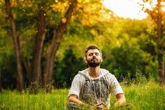 Un uomo che medita su erba verde nel parco Fotografia Stock