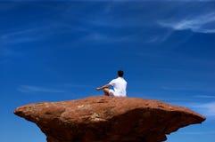 Un uomo che meditating su un'alta roccia Immagine Stock Libera da Diritti